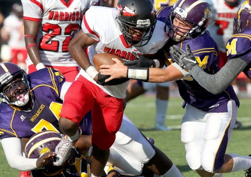 Nansemond River's Terrence Lambert is brought down by Menchville's Nicholas Webster after a short gain during the first quarter Friday at Todd Stadium.