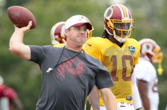 Washington Redskins quarterback Robert Griffin III watches as coach Jay Gruden throws to receivers during Thursday's training camp against the Houston Texans.
