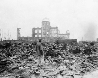 FILE - In this Sept. 8, 1945 file photo, an allied correspondent stands in the rubble in front of the shell of a building that once was a exhibition center and government office in Hiroshima, Japan, a month after the first atomic bomb ever used in warfare was dropped by the U.S. on Aug. 6, 1945. (AP Photo/Stanley Troutman, File)