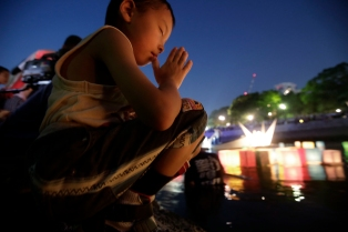 A boy offers prayer after releasing a paper lantern into the Motoyasu River where hundreds of thousands of atomic bombing victims died with the backdrop of the Atomic Bomb Dome in Hiroshima, western Japan Thursday, Aug. 6, 2015. Japan marked the 70th anniversary Thursday of the atomic bombing of Hiroshima. (AP Photo/Eugene Hoshiko)