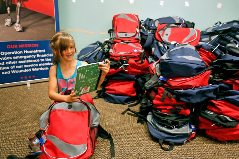 Emma Holmes smiles as she finds a notebook inside a donated backpack Saturday morning. Operation Homefront held a Back-to-School Brigade program at the Peninsula Town Center where hundreds of donated backpacks and school supplies were distributed to children of military families.