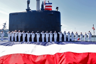 Sailors stand on the deck of the submarine USS John Warner during the commissioning ceremony at Naval Station Norfolk Saturday morning August 1, 2015.