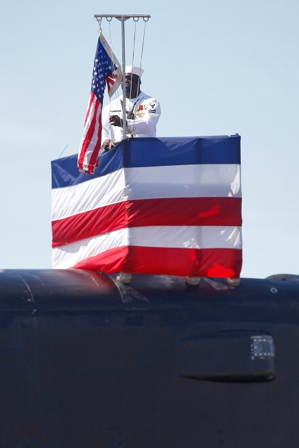 Petty Officer first class Kenric Sanderson raises the flag during the commissioning of the submarine USS John Warner at Naval Station Norfolk Saturday morning August 1, 2015.