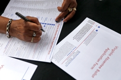 Shirley Sutton of the Hampton voter registration office readies an absentee ballot application form during a voter registration drive to commemorate the 50th anniversary of the signing of the Voting Rights Act of 1965 Thursday afternoon. The event was organized by the Hampton NAACP and held at Mary's Park in Peninsula Town Center.
