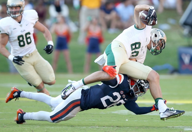 William & Mary's Christian Reeves is stopped after a short reception by Virginia's Maurice Canady during the third quarter Saturday September 19, 2015.