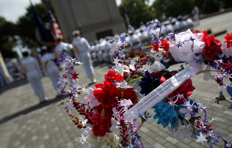 A wreath with an attached paper listing the sequence of events on September 11, 2001 is held by a USS Abraham Lincoln sailor prior to being placed beside the Victory Arch during ceremonies in Newport News on Friday September 11, 2015. (Adrin Snider)