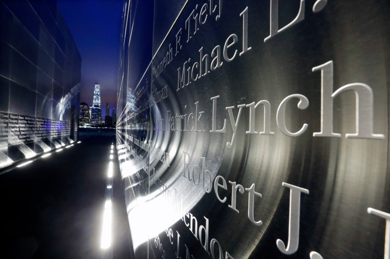 "The names are seen on the ""Empty Sky"" memorial to New Jersey's victims of the Sept. 11, 2001 terrorist attacks, as 1 World Trade Center, center left, stands on the 14th anniversary, early Friday, Sept. 11, 2015, in Jersey City, N.J.  Victims' relatives began marking the 14th anniversary of Sept. 11 in a subdued gathering Friday at ground zero, with a moment of silence and somber reading of names. (AP Photo/Mel Evans)"