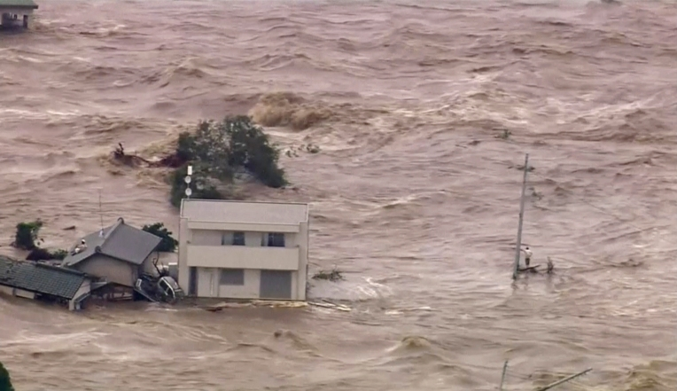 In this photo taken from video provided by Japan's Tokyo Broadcasting System (TBS) television network, a man, right, stands stranded in the middle of raging floodwaters before being rescued by a military helicopter in Joso, Ibaraki prefecture, Thursday, Sept. 10, 2015. Raging floodwaters broke through a berm Thursday and swamped the city near Tokyo, washing away houses, forcing dozens of people to rooftops to await helicopter rescues and leaving one man clinging for his life to a utility pole.  (TBS TV via AP)