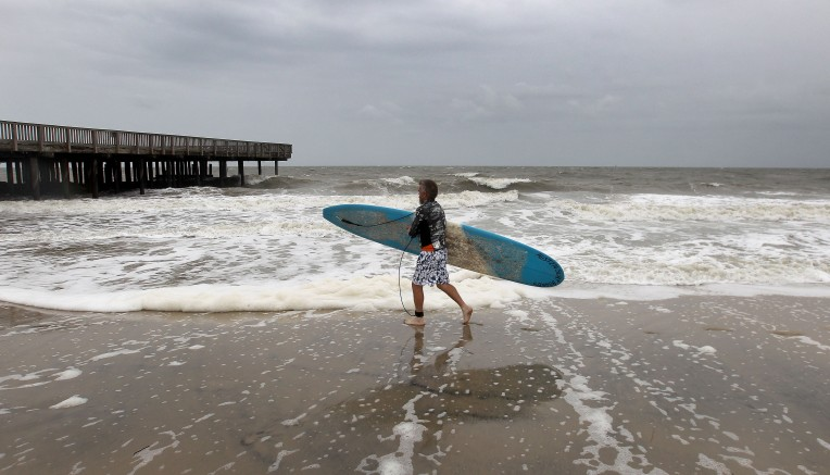 Ray Bottomley of Hampton carries his board out to Buckroe Beach in Hampton, Va.  Friday to take advantage of the high surf. An offshore storm has kicked up tides and surf on the Chesapeake Bay. (Rob Ostermaier)