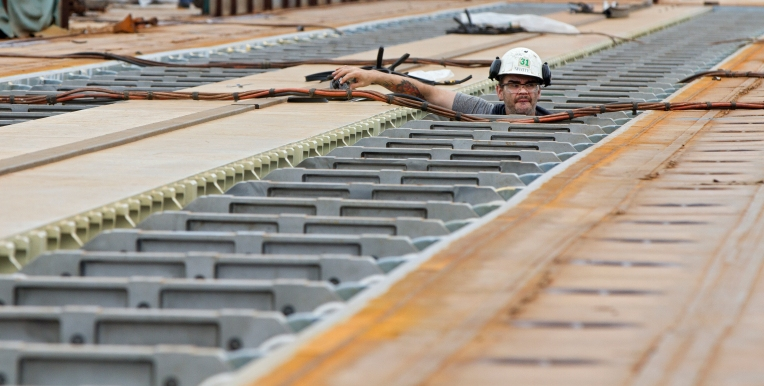 A man works underneath the catapult tracks of the aircraft carrier Gerald R. Ford on Tuesday, Sept. 22, 2015 at Newport News Shipbuilding. (Kaitlin McKeown)