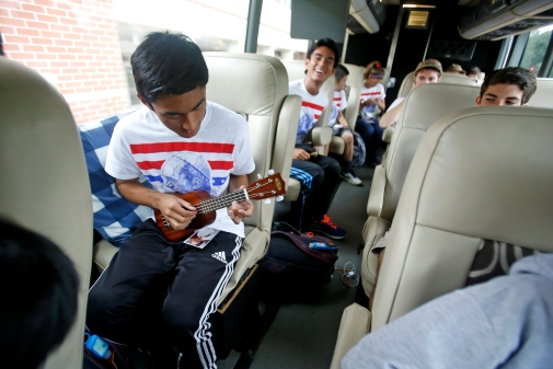 Peninsula Catholic High School student Miggy Almirante plays the ukulele while sitting on a bus Friday morning September 25, 2015. Twenty five students are traveling to Philadelphia to see Pope Francis. (Jonathon Gruenke)