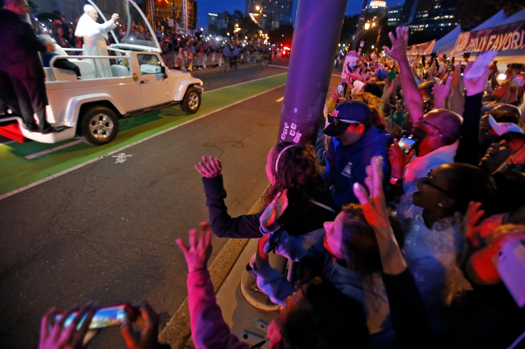 Peninsula Catholic High School students wave as Pope Francis passes by on Benjamin Franklin Parkway in downtown Philadelphia Saturday evening September 26, 2015. (Jonathon Gruneke)
