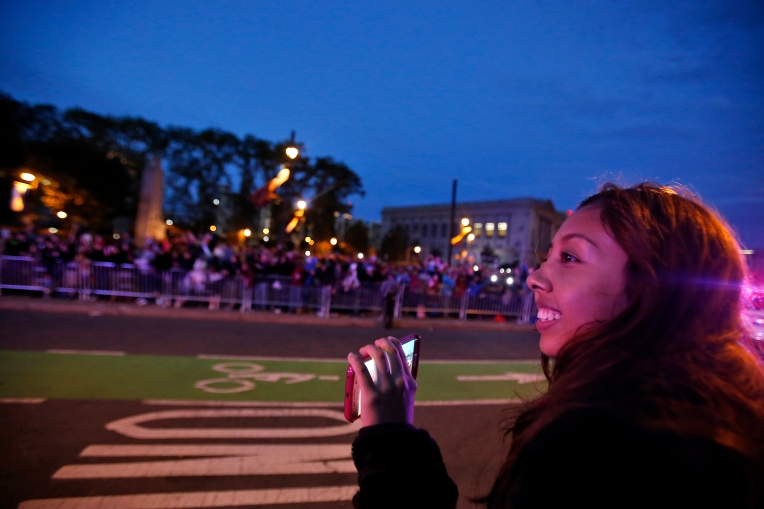 Peninsula Catholic High School student Heidi Caisachana smiles and takes photos as Pope Francis passes by on Benjamin Franklin Parkway in downtown Philadelphia Saturday evening September 26, 2015. (Jonathon Gruenke)