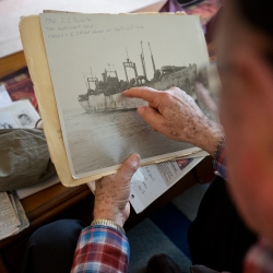 Hampton resident and World War II veteran Ken Bernstrom looks at a photo of the S.S. Bonita, a merchant ship on which he traveled home at the end of the war in 1946. (Kaitlin McKeown)