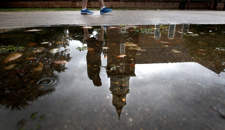 Bruton Parish is reflected in a puddle along Duke of Gloucester Street Tuesday as rain moves into the area. Rain is expected in the area most of this week as a storm threatens offshore. (Rob Ostermaier)