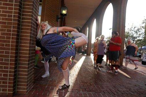 Chris Wharton stretches before participating in the Drag Race on Queens Way during Saturday's Hampton Block Party. Four teams representing different charities ran down Queens Way in heats.
