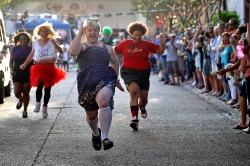 Chris Wharton races past other runners while competing in the Drag Race on Queens Way during Saturday's Hampton Block Party. Four teams representing different charities ran down Queens Way in heats.