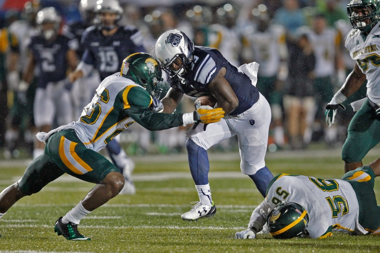 Old Dominion University's Ray Lawry, center, runs through the tackles of Norfolk State University's Leroy Parker, left, and Justin Grant, right, during Saturday's game at Ballard Stadium on September 12, 2015.