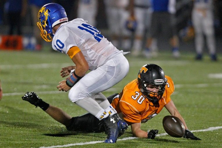 Tabb's Jacob Baylor dives after Hopewell quarterback Cameren Hill fumbles the ball during Thursday's game at Bailey Field on September 3, 2015.