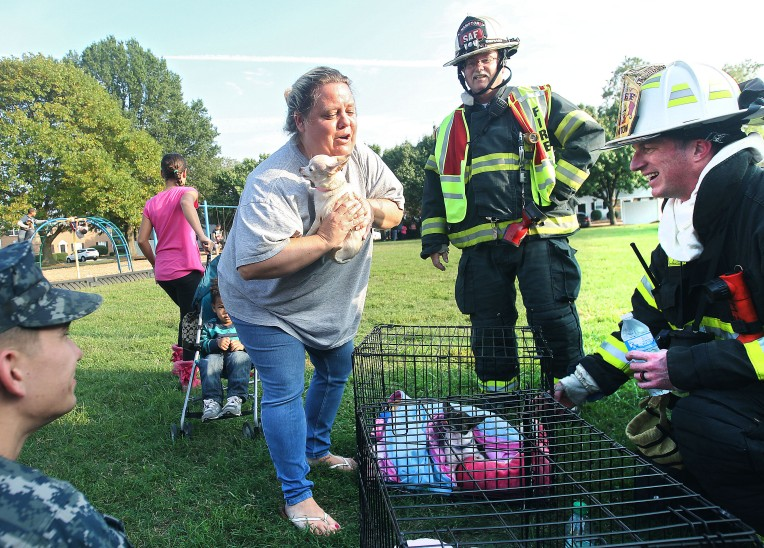 Lori Fernandez is reunited with her dog Minnie after it was pulled from her burned out home in the Cambridge Apartment complex in Hampton Thursday.