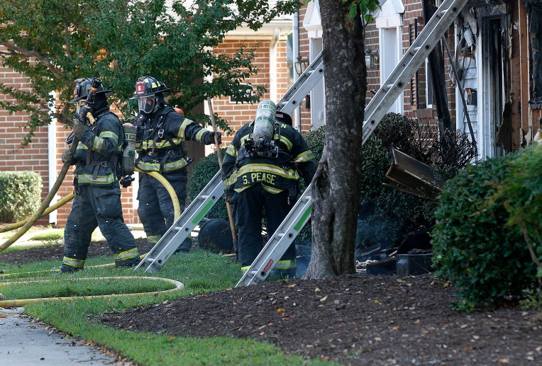 Hampton firefighters work on knocking out hotspots after a fire in the Cambridge Apartments Thursday.