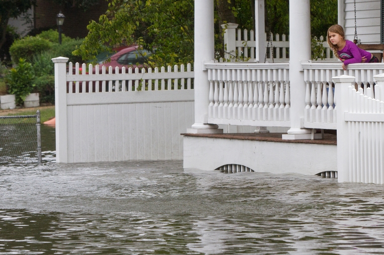 A young girl looks out from a porch as floodwaters rise along East Pembroke Avenue on Sunday afternoon in Hampton.