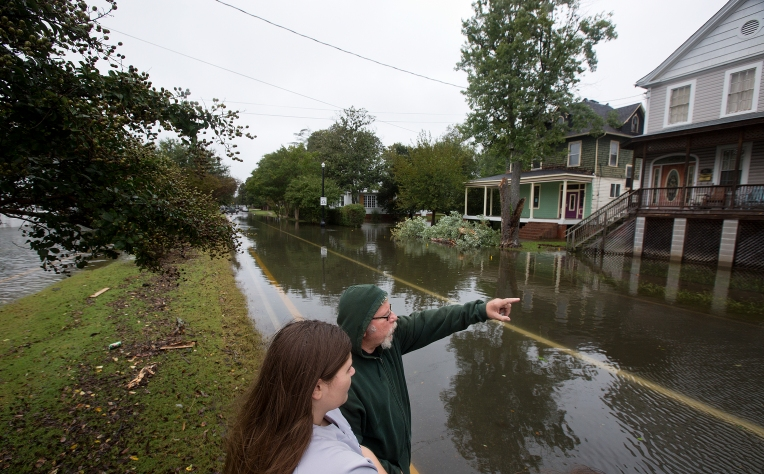 Skyeler Seals and U.R. Mills stand in the middle of floodwaters on Pembroke Avenue on Sunday afternoon in Hampton.