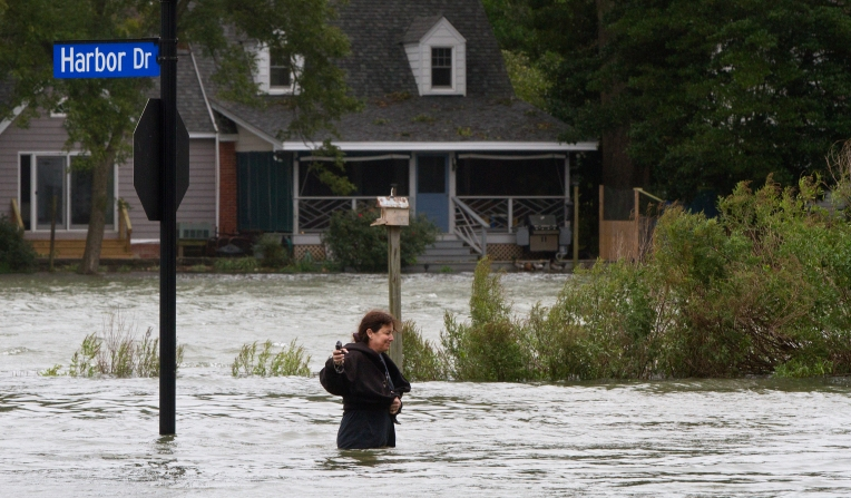 A woman walks through floodwaters on Harbor Drive near high tide on Sunday afternoon in Hampton.