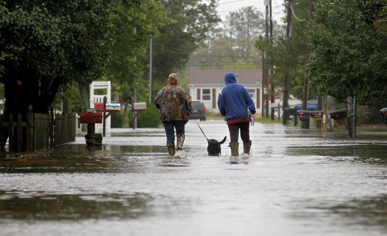 Melissa and Heath King take Molly for a walk down a flooded Lodge Rd. in Poqouson Friday afternoon October 2, 2015.