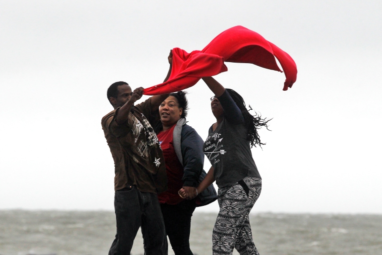 Donnell Robinson, left, Kyra Lanier, center, and Trinity Lanier attempt to wrangle a coat as wind gusts move across Buckroe Beach Friday afternoon October 2, 2015. (Jonathon Gruenke)