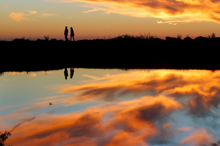 John Dinio, left, and Joy Dinio walk along the James River as the sun begins to set Tuesday evening October 20, 2015.