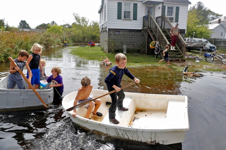 Ryan West, center, paddles a boat with other children through rising flood water in Poquoson Saturday afternoon October 3, 2015.