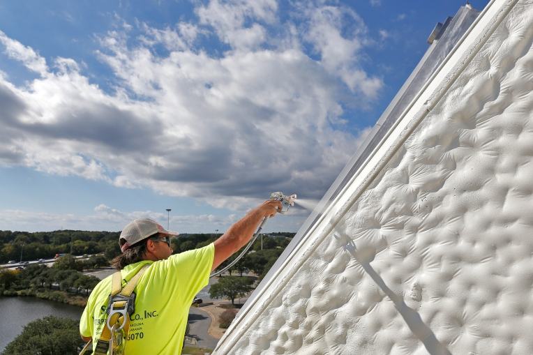 Todd Lorenz of Strickland Waterproofing Company Inc. paints the exterior of the Hampton Coliseum Wednesday afternoon October 7, 2015.