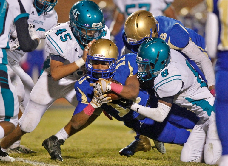 Phoebus' Jomari Becnel, center, dives for the end zone through Woodside's Conrad Outlaw, left, and Kamari Jackson during Friday's game at Darling Stadium October 23, 2015.