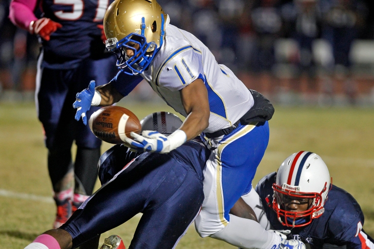 Phoebus' Jomari Becnel, center, bobbles the ball while being hit by Denbigh's Joseph Taylor, left, and Ronald Livingston, right, during Thursday's game at Todd Stadium October 29, 2015.