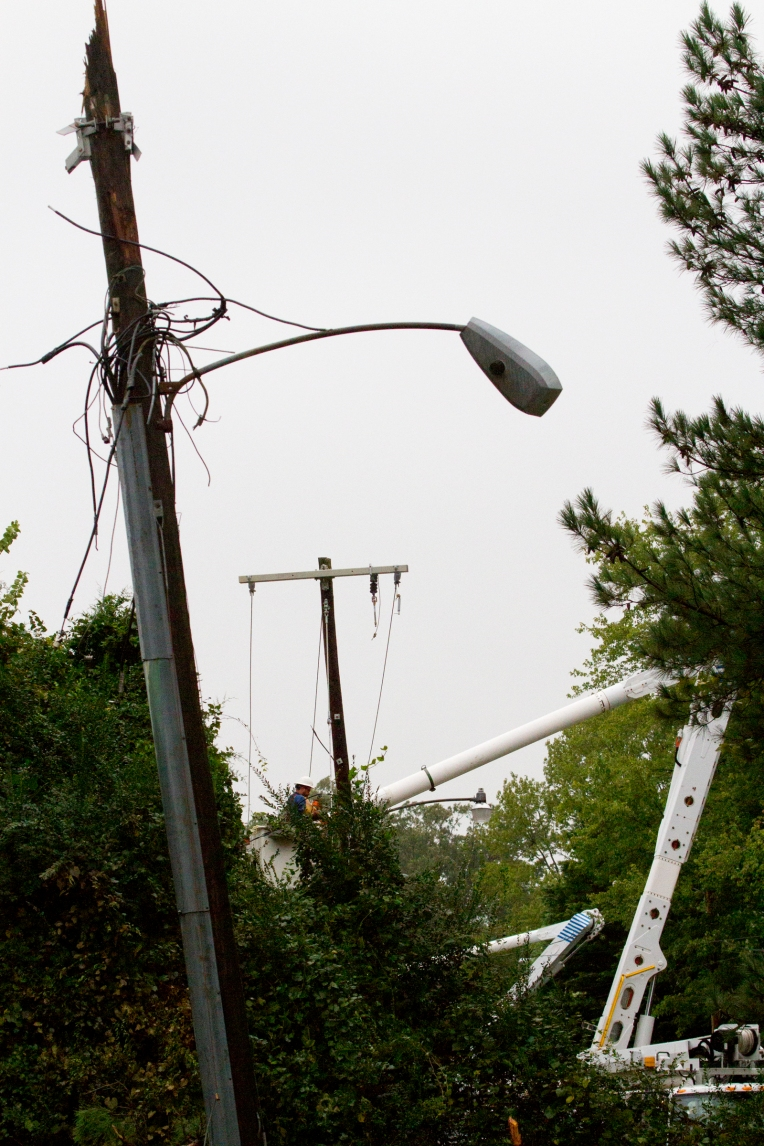 Dominion Power crews work a power outage on Mennonite Lane in Newport News on Sunday Oct. 4, 2015 after a pine tree fell breaking a utility pole downin power lines.
