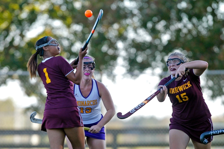Warwick's Cheyenne Robertson, left, and Ashleigh-Page Norton, right, battle for the ball with Menchville's Lauren Leach during Wednesday's game on October 14, 2015.