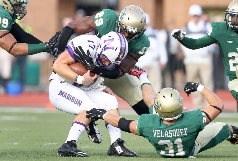 James Madison quarterback Bryan Schor is brought down by William & Mary's Marcus Harvey (29) and Jared Velasquez (31) as he tries to scramble during the first quarter Saturday October 31, 2015 at Zable Stadium.