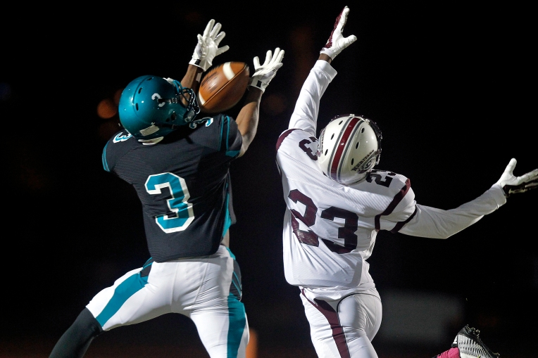 Woodside's Jacari Lee just misses catching the ball around Heritage's Craig Long during Friday's game at Todd Stadium October 30, 2015.