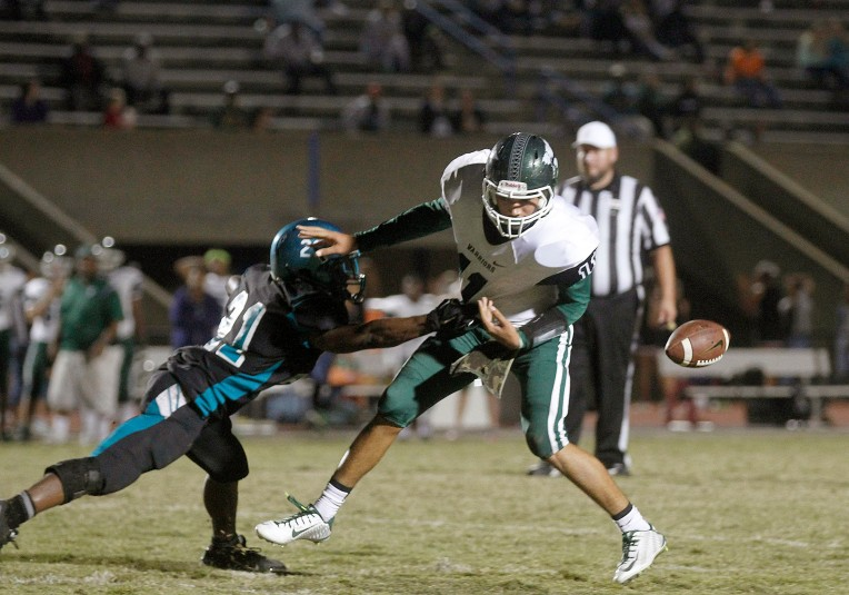 Woodside's D'Angelo Chesson knocks the ball away from Kecoughtan quarterback Desmond Savage during the fourth quarter Friday November 6, 2015. Chesson recovered the ball and returned it to the Kecoughtan 13 yard line setting up a go-ahead field goal late in the fourth.