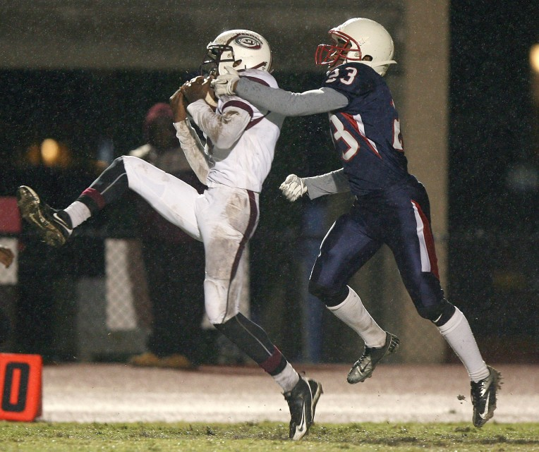Heritage's Timothy Payne makes this long reception under pressure from Denbigh's  Teaunce Collins during the second quarter Saturday November 7, 2015 at Todd Stadium.