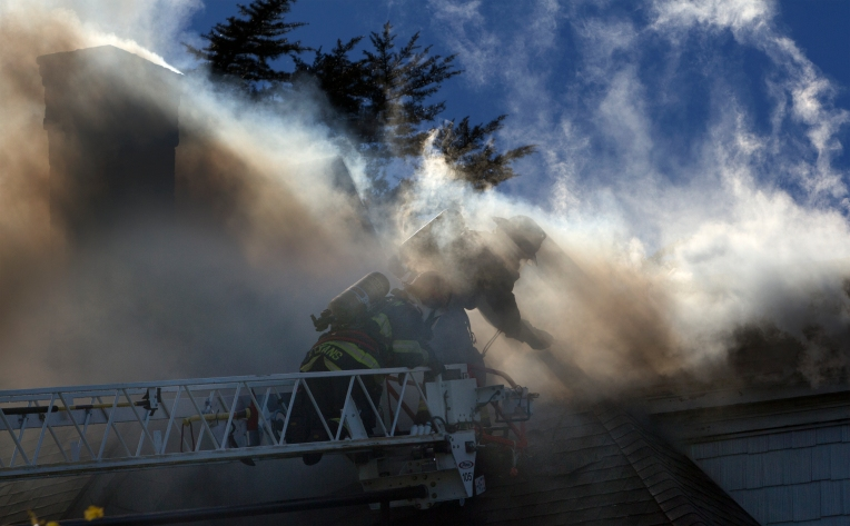 Firemen work in heavy smoke to battle a blaze in Hampton, Va. on Chesapeake Ave. around midday Friday, Nov 20, 2015. The home, located in the Olde Wythe section suffered heavy damage. The home was built in 1899. Origin and cause of the fire is under investigation. (Adrin Snider