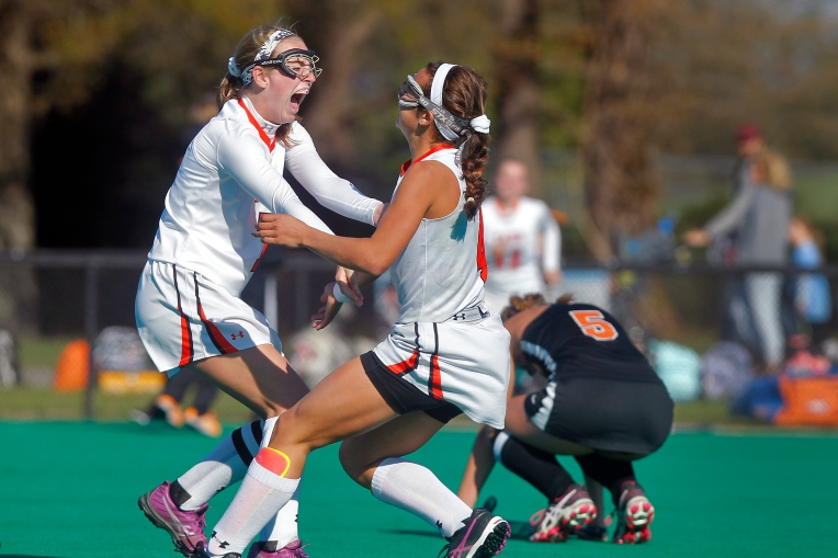 Tabb's Courtney Fiest, left, and Maya Denison celebrate winning as James Monroe's Rebecca Hamlett, right, collapses during Saturday's 4A state championship game at the National Field Hockey Training Center in Virginia Beach on November 14, 2015.