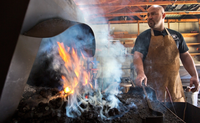 George Cramer is the owner of the Village Blacksmith shop at Gloucester Courthouse. George loves to work with iron inside his blacksmithing shop in Gloucester Village.  George is starting up his fire to make his colonel type Creset Fire Basket for orders inside his blacksmithing shop.