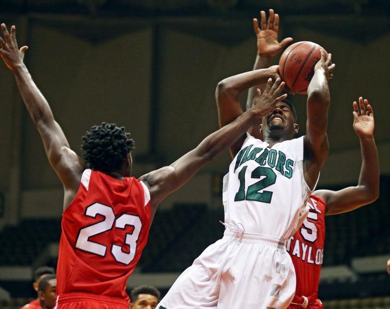 Lake Taylor's Emmanuel Cuffee (23) attempts to block Kecoughtan's Taiwan Drummond (12) during their game held at the Hampton Coliseum on Tuesday, Dec. 29, 2015.