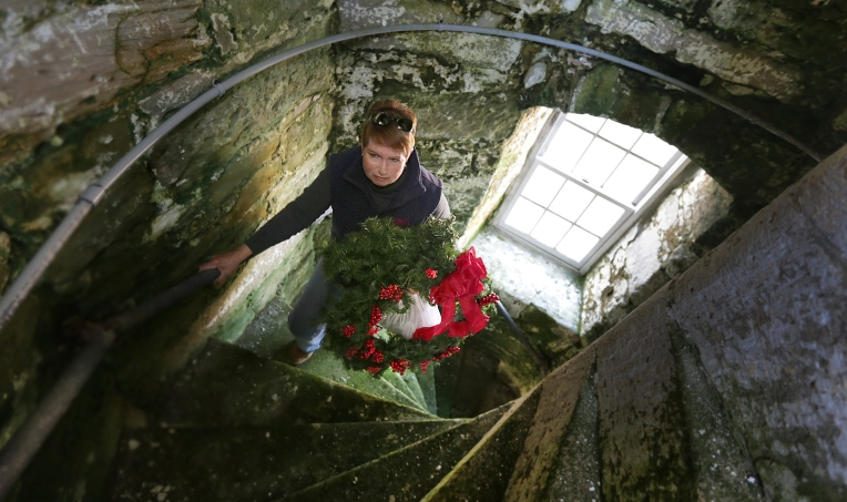 Carrying a wreath and a bag of roping, Barbara Bauer walks up to the top of  Old Point Comfort Lighthouse at Ft. Monroe. Bauer loves the lighthouse and volunteers to clean and decorate it.