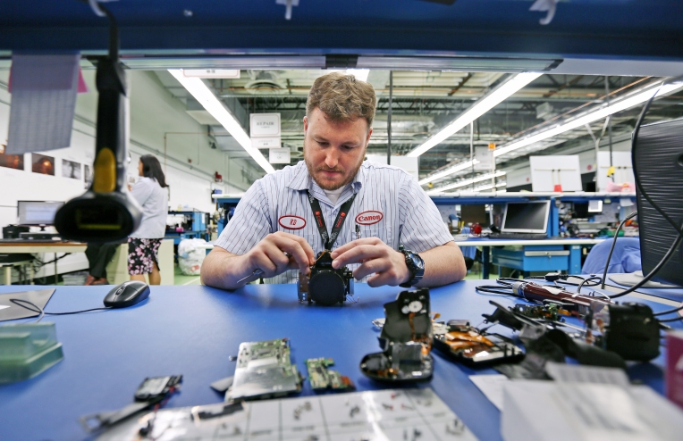Camera Master Craftsman RD Meyers dissembles a canon point and shoot camera while working at Canon Virginia, Inc. on Monday, Dec. 14, 2015.