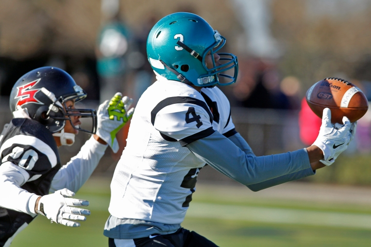 Peninsula's Jacari Lee, right, just misses catching the ball around Southside's Tracey Martin, left, during Saturday's Nike 757 All-Star Classic football at Powhatan Field on December 19, 2015.