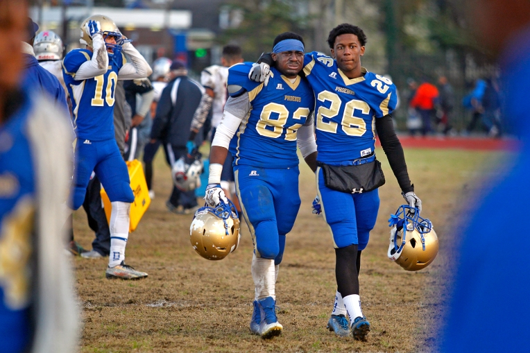 Phoebus' Marcus Taite, center, and Berry Hargrave, right, walk off the field after losing to Magna Vista 28-23 during Saturday's 3A state semifinal game at Darling Stadium on December 5, 2015.