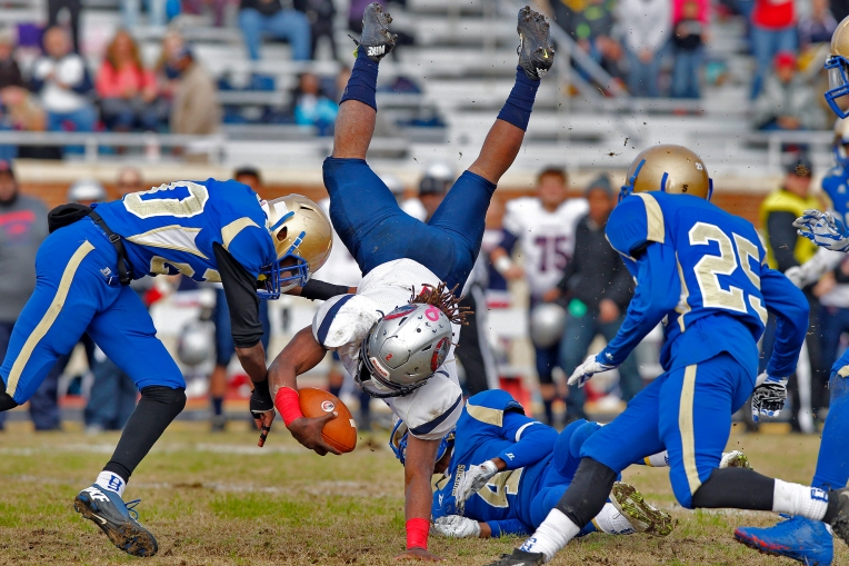 Phoebus' Damion Charity, ledt, Daquan Lewis, center, and Aaron Branch, right, attempt to bring down Magna Vista's Jacqez Hairston during Saturday's 3A state semifinal game at Darling Stadium on December 5, 2015.